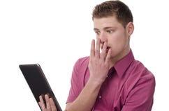 Hombre joven que lee noticias impactantes en la tablilla. Foto de archivo