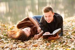 Hombre joven que lee a su novia Foto de archivo libre de regalías