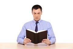 Hombre joven que lee un libro Imágenes de archivo libres de regalías