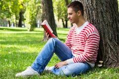 Hombre joven que lee un libro Imagenes de archivo