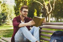Hombre joven que lee un libro al aire libre Fotos de archivo