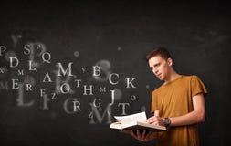 Hombre joven que lee un libro con las letras del alfabeto Fotos de archivo