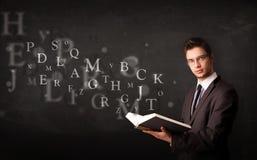 Hombre joven que lee un libro con las letras del alfabeto Imagen de archivo libre de regalías