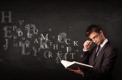 Hombre joven que lee un libro con las letras del alfabeto Imagen de archivo