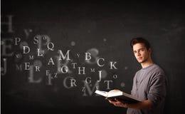 Hombre joven que lee un libro con las letras del alfabeto Imágenes de archivo libres de regalías