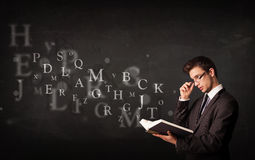 Hombre joven que lee un libro con las letras del alfabeto Fotos de archivo libres de regalías