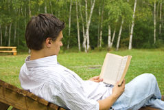 Hombre joven que lee un libro en el parque Fotografía de archivo libre de regalías
