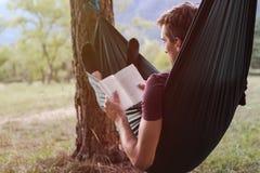 Hombre joven que lee un libro en una hamaca imagen de archivo