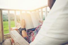 Hombre joven que lee un libro que miente en cama relajante en la terraza con g Imagen de archivo libre de regalías