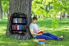 Hombre joven que lee un libro que se sienta en la hierba verde que se inclina en un árbol en el parque Imagenes de archivo