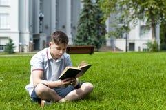 Hombre joven que lee un libro que se sienta en la hierba Imagen de archivo libre de regalías