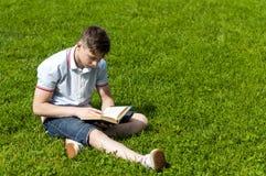Hombre joven que lee un libro que se sienta en la hierba Imágenes de archivo libres de regalías