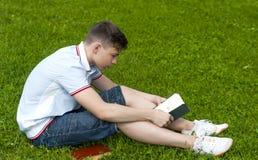 Hombre joven que lee un libro que se sienta en la hierba Fotos de archivo