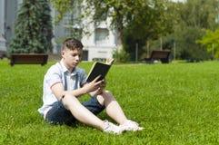 Hombre joven que lee un libro que se sienta en la hierba Fotos de archivo libres de regalías