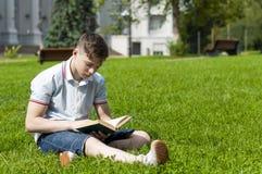 Hombre joven que lee un libro que se sienta en la hierba Foto de archivo libre de regalías
