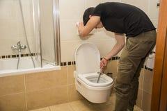 Hombre joven que limpia el servicio del cuarto de baño, limpiando Fotografía de archivo libre de regalías