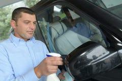 Hombre joven que limpia exactamente miror de los coches foto de archivo libre de regalías