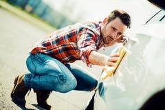 Hombre joven que limpia su coche al aire libre imagenes de archivo