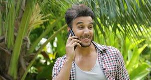 Hombre joven que llama usando el teléfono elegante de la célula que sonríe al aire libre árboles de Guy Closeup Speaking Over Gre almacen de metraje de vídeo