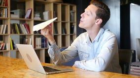 Hombre joven que lleva a cabo el avión de papel, pensando una idea almacen de video
