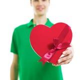 Hombre joven que lleva a cabo el corazón rojo Foto de archivo libre de regalías