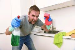Hombre joven que lleva a cabo el espray detergente de la limpieza y esponja que lava enojado limpio de la cocina casera en la ten Fotografía de archivo libre de regalías