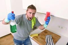 Hombre joven que lleva a cabo el espray detergente de la limpieza y esponja que lava enojado limpio de la cocina casera en la ten Foto de archivo libre de regalías