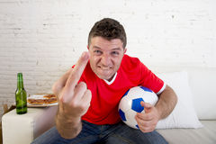 Hombre joven que lleva a cabo el partido de fútbol de observación de la bola en la TV que gesticula trastorno y enojado loco dand Imagen de archivo
