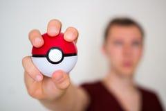 Hombre joven que lleva a cabo el pokeball Foto de archivo libre de regalías