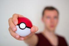 Hombre joven que lleva a cabo el pokeball Imagen de archivo libre de regalías