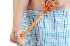 Hombre joven que lleva a cabo la cinta métrica, midiendo su pene