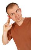 Hombre joven que lleva a cabo la mano en su oído fotos de archivo libres de regalías