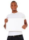 Hombre joven que lleva a cabo la muestra blanca en blanco Fotografía de archivo libre de regalías