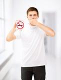 Hombre joven que lleva a cabo la muestra de no fumadores Imagenes de archivo