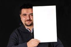 Hombre joven que lleva a cabo la muestra en blanco. Fotografía de archivo libre de regalías
