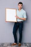 Hombre joven que lleva a cabo a la tarjeta en blanco Foto de archivo libre de regalías