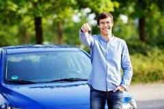 Hombre joven que lleva a cabo llave de su nuevo coche foto de archivo