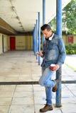 Hombre joven que lleva a cabo smartphone y la taza de coffe Fotos de archivo libres de regalías