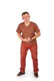 Hombre joven que lleva a cabo sus manos en su estómago con dolor Imagen de archivo libre de regalías