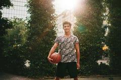 Hombre joven que lleva a cabo un baloncesto en corte al aire libre Imagen de archivo