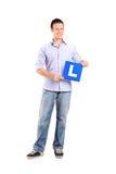 Hombre joven que lleva a cabo un l muestra Foto de archivo libre de regalías