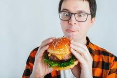 Hombre joven que lleva a cabo un pedazo de hamburguesa el estudiante come los alimentos de preparación rápida La hamburguesa no e fotos de archivo libres de regalías