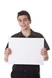 Hombre joven que lleva a cabo a una tarjeta en blanco Imagen de archivo libre de regalías