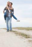 Hombre joven que lleva a cuestas a la mujer en rastro en el campo Imagenes de archivo