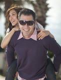 Hombre joven que lleva a cuestas a su novia Fotos de archivo