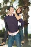 Hombre joven que lleva a cuestas a su novia Imagen de archivo libre de regalías