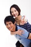 Hombre joven que lleva a cuestas a su novia bonita Foto de archivo libre de regalías