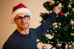 Hombre joven que lleva el sombrero de santa que adorna el árbol de navidad con la luz Foto de archivo