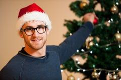 Hombre joven que lleva el sombrero de santa que adorna el árbol de navidad con la luz Imagen de archivo libre de regalías