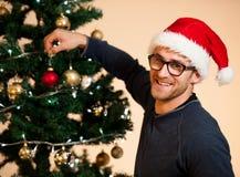 Hombre joven que lleva el sombrero de santa que adorna el árbol de navidad con la luz Imagenes de archivo